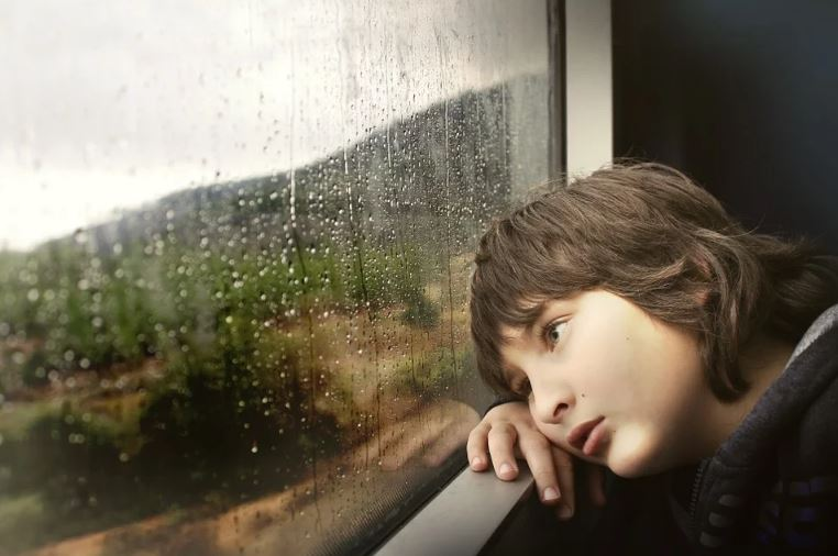 boy child looking out of the window at the rain