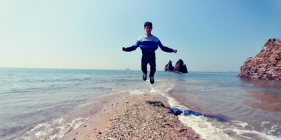 child jumping on the beach