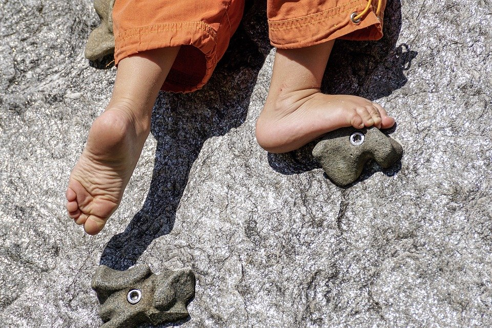 child's feet rock climbing